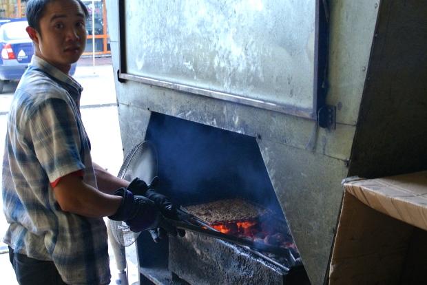 Tady se griluje křupavý bůček na Bun Cha. Vedle restaurace.