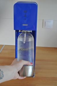 6. Do hrdla nasuňte lahev plnou vody a tlakem zpět směrem k výrobníku uveďte spolu s hrdlem do svislé polohy. Uslyšíte cvaknutí a tím je vše připraveno k použití.